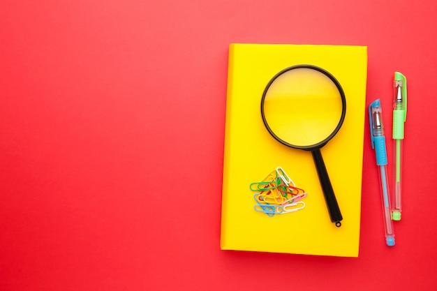 Libri di scuola gialli con la penna e la lente su fondo rosso