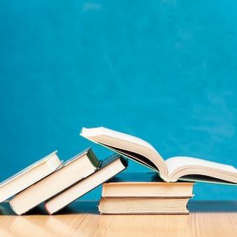 Libri di vista frontale sulla tavola con fondo blu