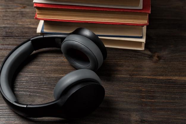 Libri e cuffie stereo. ascolta la musica e leggi. sfondo in legno, primo piano