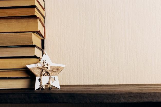 Libri e un albero di natale con coni e una decorazione a stella su una vecchia mensola in legno.
