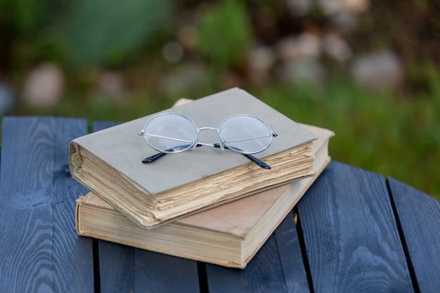 Libri e vetri d'annata sulla tavola di legno in un giardino di tempo di primavera