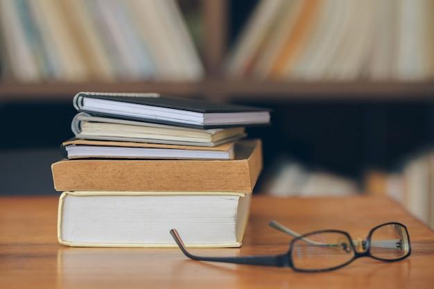 Libri impilati e bicchieri sul vecchio tavolo di legno in biblioteca.