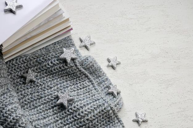 Libri invernali, sciarpa grigia lavorata a maglia, ghirlanda splendente e stelle decorative argentate