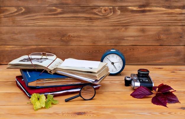 Libri, orologio e macchina fotografica su legno