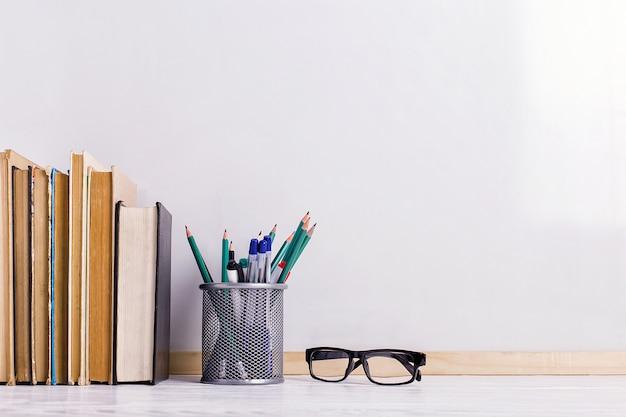 Libri, pennarelli, quaderno, matita e bicchieri sul tavolo