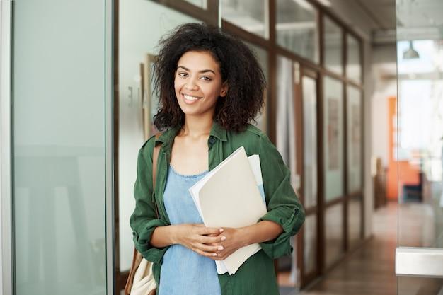 Libri sorridenti della tenuta della bella studentessa africana allegra in università. concetto di educazione.