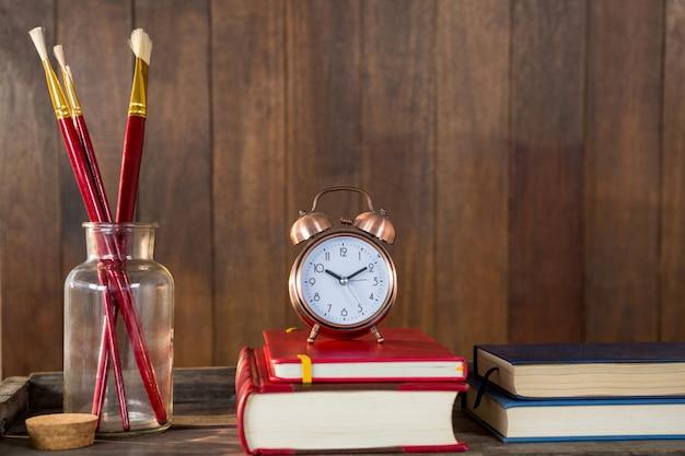 Libri, sveglia e pennello disposti su tavola di legno