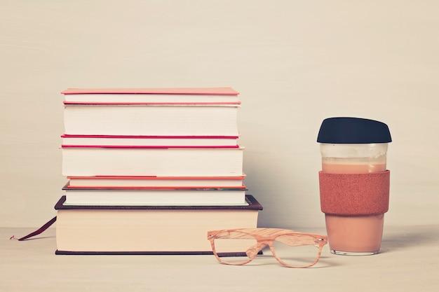 Libri, tazza di caffè, occhiali da lettura