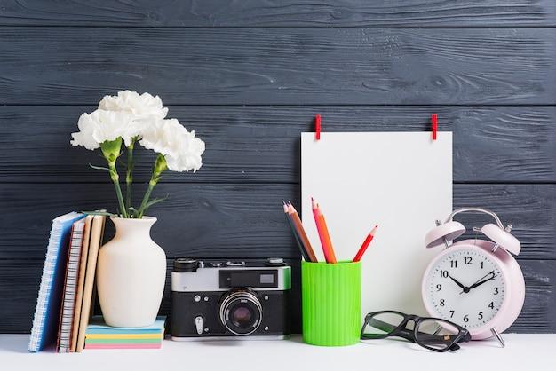 Libri; vaso; macchina fotografica d'epoca; occhiali; portamatite e carta bianca bianca su fondale in legno