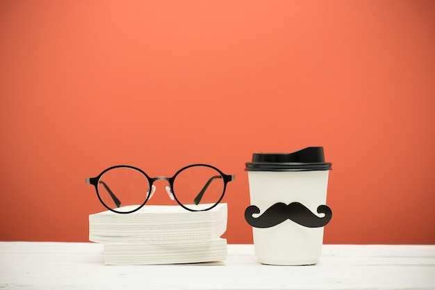 Libri, vetri e tazza con i baffi sulla tavola di legno su fondo dell'annata arancione