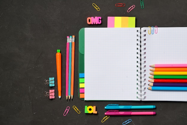 Libro aperto con forniture per ufficio e studenti su gesso nero