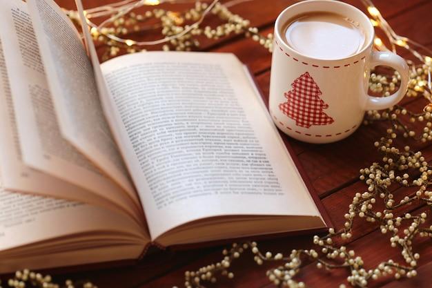 Libro aperto con tazza di natale e ornamenti
