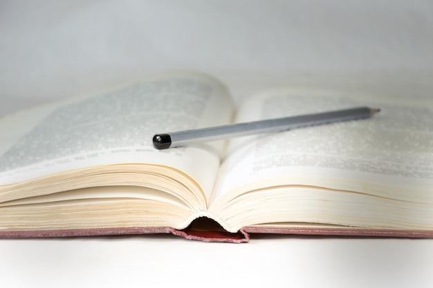 Libro aperto con una matita, illuminato da un raggio di luce.