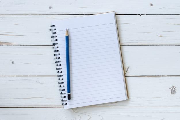 Libro aperto di vista superiore sul tavolo di legno con la matita.