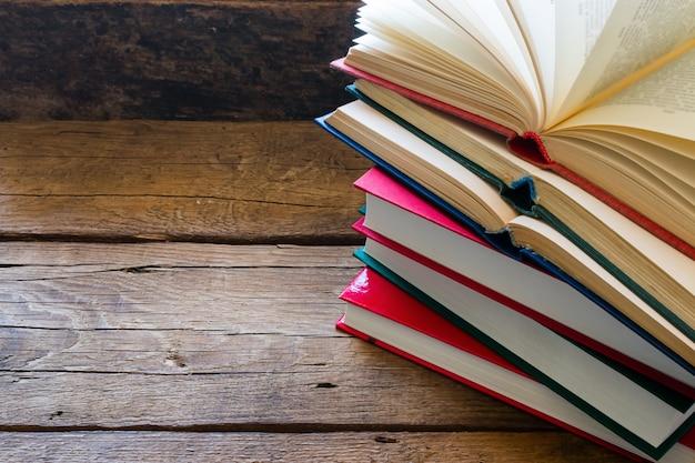 Libro aperto su una pila di libri chiusi con spazio per il testo