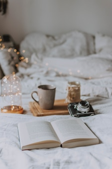 Libro aperto, una macchina fotografica, un vassoio e una tazza su un letto con lenzuola bianche
