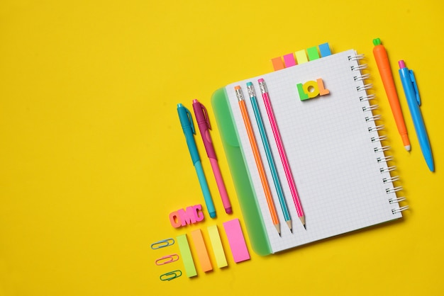 Libro aperto variopinto della copia con i rifornimenti dello studente e dell'ufficio su gesso giallo. spazio per il testo.