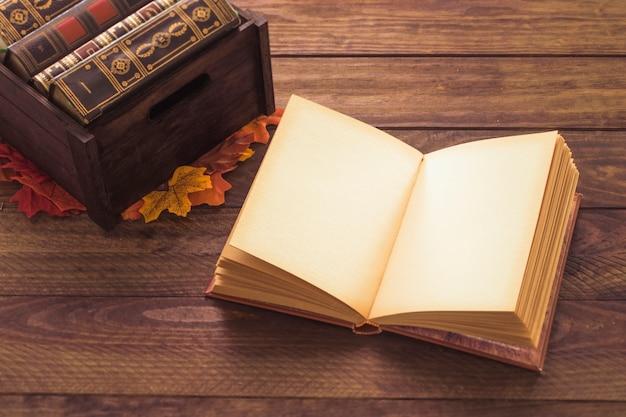 Libro aperto vicino a foglie e scatola