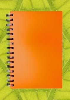 Libro arancione in bianco su sfondo foglia