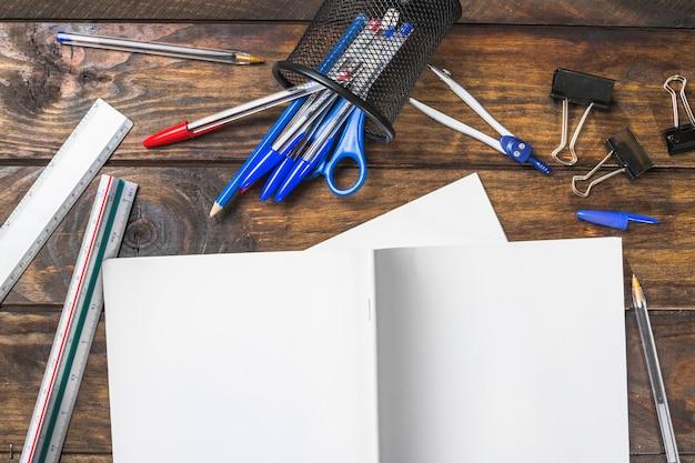 Libro bianco con cartolerie su fondale in legno