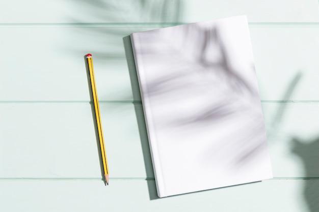 Libro bianco e matita di vista superiore con ombra delle foglie