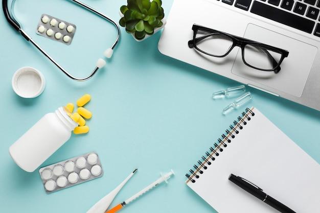 Libro bianco in bianco con la lavagna per appunti e la penna vicino allo stetoscopio sopra fondo blu
