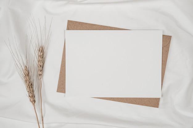 Libro bianco in bianco sulla busta di carta marrone con fiore secco d'orzo sul panno bianco
