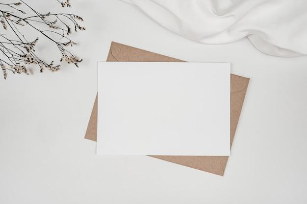 Libro bianco in bianco sulla busta di carta marrone con fiore secco di limonium su panno bianco