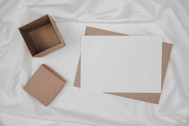 Libro bianco in bianco sulla busta di carta marrone e sulla scatola di cartone messa su un panno bianco