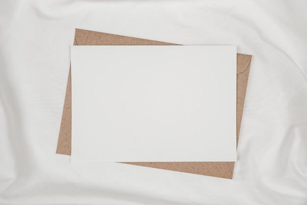 Libro bianco in bianco sulla busta di carta marrone sul panno bianco