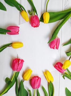 Libro bianco per il testo e il mazzo di tulipani di colore su fondo di legno.