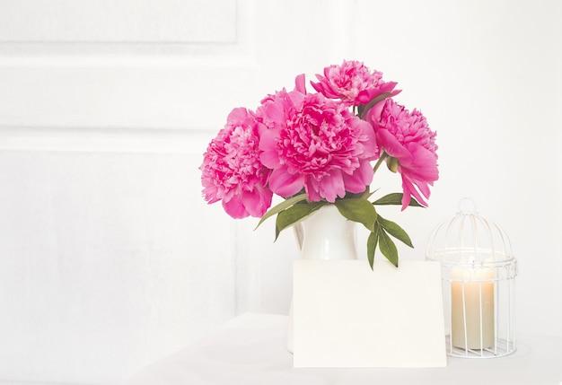 Libro bianco per testo di invito e peonie in un vaso