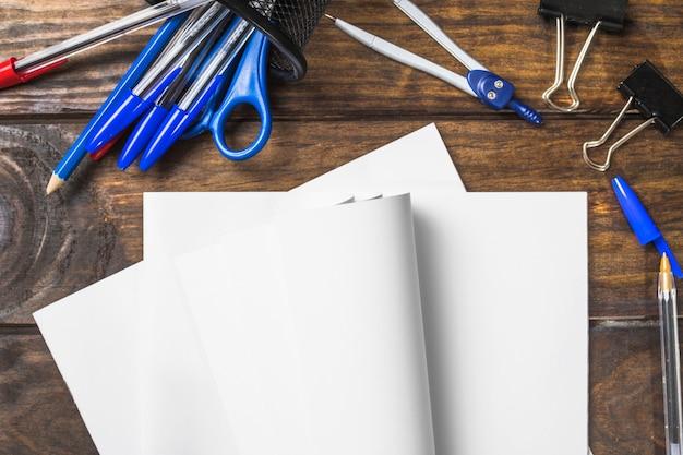 Libro bianco piegato con le cancellerie sul tavolo di legno