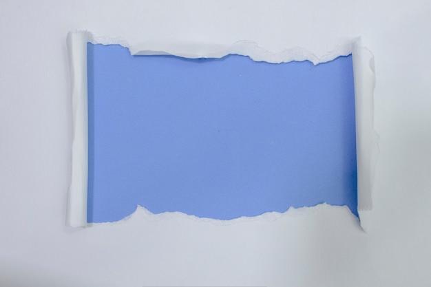 Libro bianco strappato sopra il fondo blu di colore