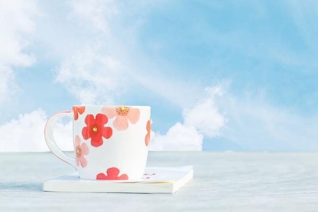 Libro bianco sveglio della tazza del primo piano sullo scrittorio con la bella priorità bassa del cielo blu