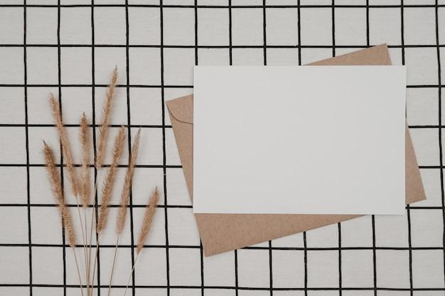 Libro bianco vuoto su busta di carta marrone con fiore secco di coda di volpe ispida e scatola di cartone su panno bianco con motivo a griglia nera