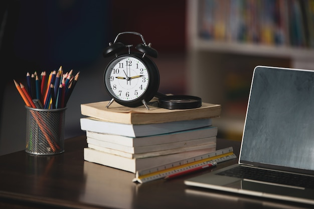 Libro, computer portatile, matita, orologio sulla tavola di legno in biblioteca, istruzione che impara concetto