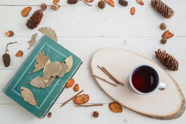 Libro d'annata e bevanda in retro tazza sulla tavola di legno. vista dall'alto