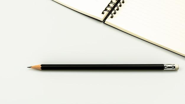 Libro del diario e una matita sul fondo bianco dello scrittorio con lo spazio della copia