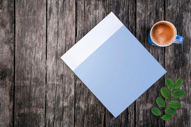 Libro della copertura in bianco del modello e tazza di caffè blu su vecchio fondo di legno.