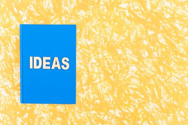 Libro di copertura blu di idee su fondo giallo