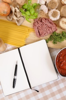 Libro di cucina con ingredienti per spaghetti alla bolognese