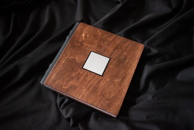 Libro di legno con una targa dati su uno sfondo di tessuto nero.