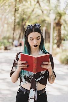 Libro di lettura alla moda della giovane donna nel parco