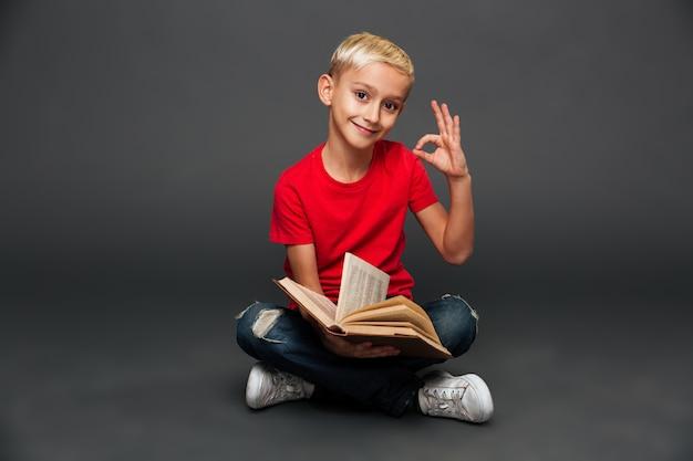 Libro di lettura allegro del bambino del ragazzino che mostra gesto giusto.