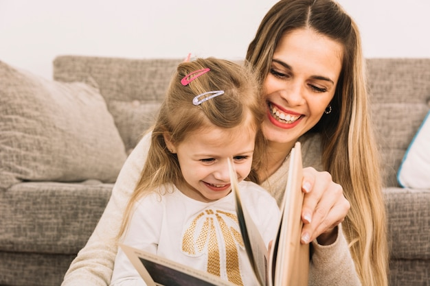 Libro di lettura allegro della figlia e della madre vicino al sofà