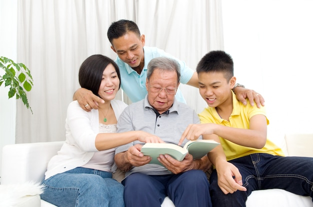 Libro di lettura asiatico della famiglia a casa