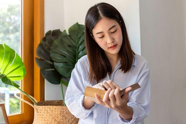 Libro di lettura asiatico della ragazza vicino alla finestra. tempo di rilassamento.