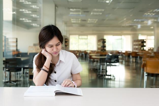 Libro di lettura asiatico dello studente in aula all'università.
