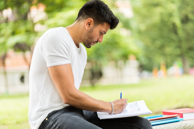 Libro di lettura bello del giovane sul banco nel parco
